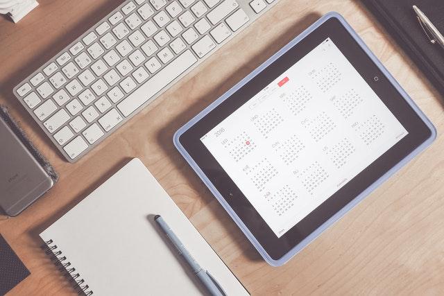 ein Holzschreibtisch mit einem Notizbuch, einem schwarzen Filzstift, einer Tablet auf dem ein Kalender zu sehen ist und einem weißen Keyboard