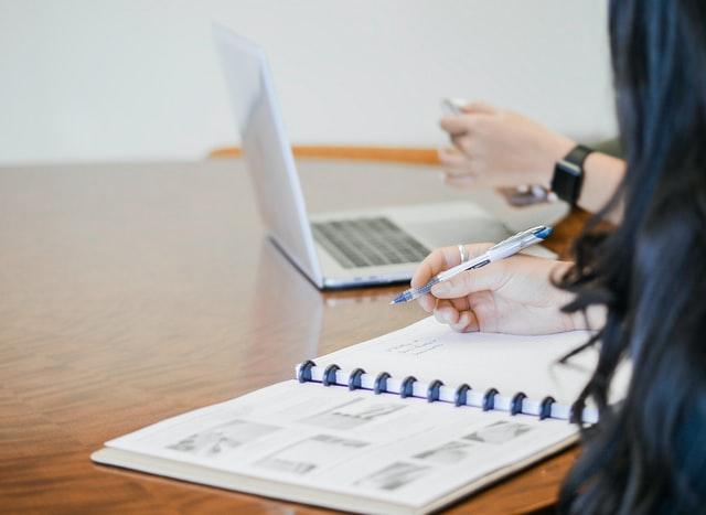 ein Holztisch auf dem ein silberner Laptop und ein offener DINA4 Kalender liiegen und die Hand einer Person mit einem blauem Kugelschreiber