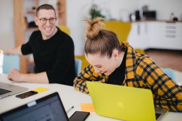 zwei Studenten, ein junger Mann und eine junge Frau die zusammen an einem Tisch mit Heften und Computer sitzen und lachen