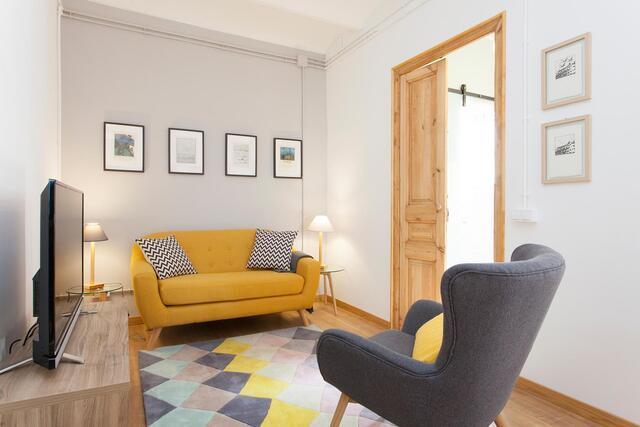 wohnzimmer mit grauen und weißen wänden, naturholz tür und türrahmen, senffarbenes zweisitzer sofa und grauer einsitzer und ein bunter teppich