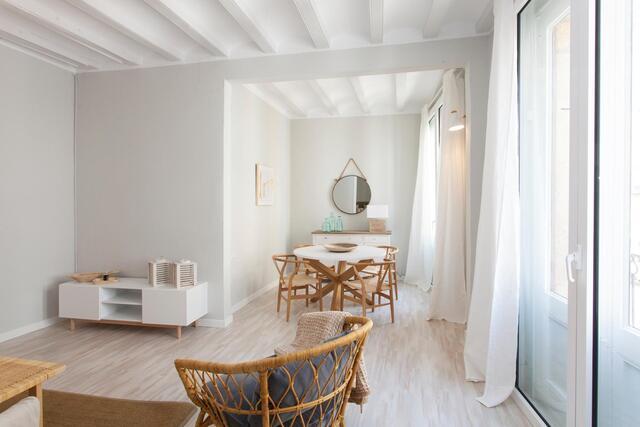 Wohn-Esszimmer einer Wohnung, heller parkettboden, Holzstühle, weiße Vorhänge und Tische und eine in grautönen gestrichene Wand