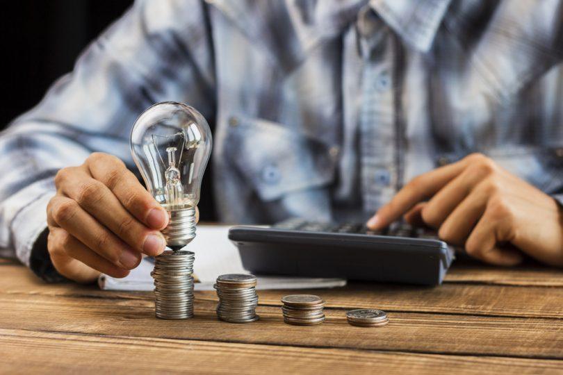 ein Mann mit einem kariertem Hemd der auf etwas auf einem Taschenrechner ausrechnet, in der anderen Hand hält er eine Glühbirne auf einen Münzturm