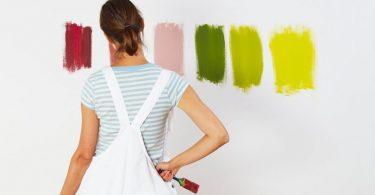 eine frau von hinten mit grün-weiß gestreiftem T-shirt und weißer Latzhose die vor eine weißen Wand mit verschiedenen Farbproben steht