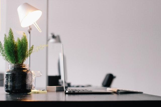 Schreibtisch auf dem ein offener Laptop, eine Pflanze in einem Glas und eine eingeschaltete Stehlampe steht