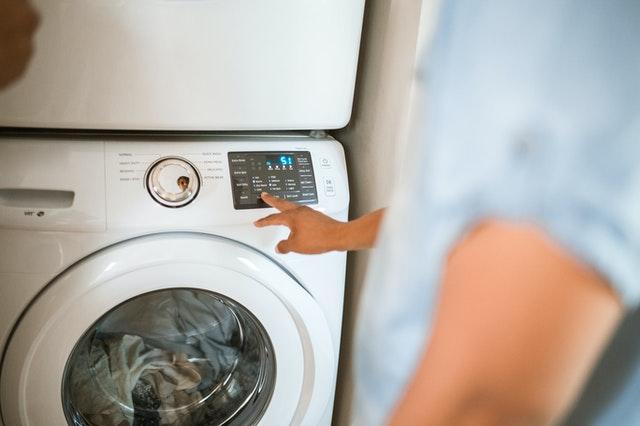 eine Person in blauem Hemd die gerade eine Waschmaschine einschaltet