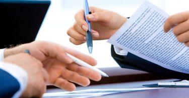 zwei Hände von zwei verschiedenen Personen die beide einen Kugelschreiber halten und sich verschiedene Dokumente ansehen