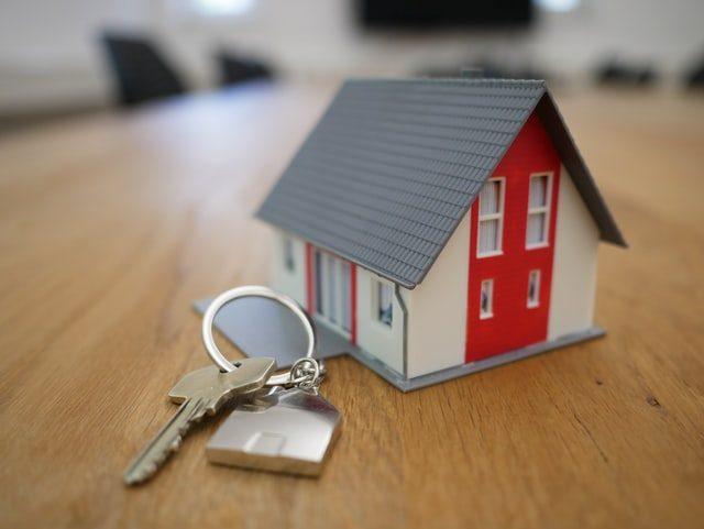 ein kleines weiß-rotes Plastikaus und ein Schlüssel auf einem Holztisch