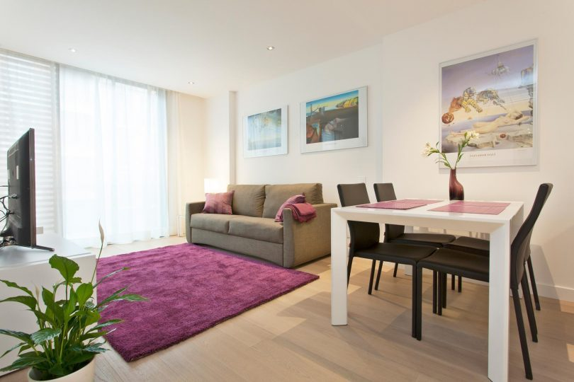Wohn/Esszimmer mit weißem Tisch, schwarzen Stühlen, ein graues Sofa, davor ein lilaner Teppich
