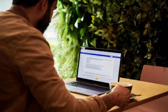 ein Mann der in einem Cafe an einem Tisch sitzt, einen Kaffee trinkt und ein Dokument in seinem Laptop ausfüllt