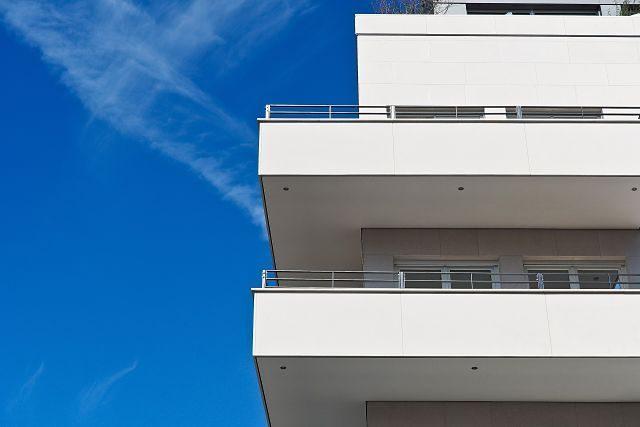 vor einem strahlend blauem Himmel sind die Ecken zweier Balkone eines weißen Hochhauses zu sehen