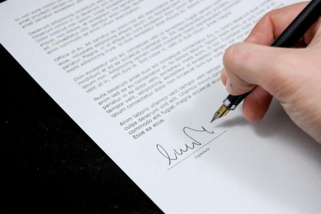 Hand mit Füller und einem Vertrag der gerade unterschrieben wird