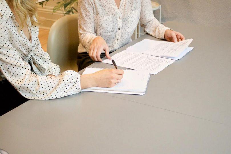 zwei Frauen mit weißen Blusen die an einem Tisch sitzen und einen Mietvertrag unterschreiben