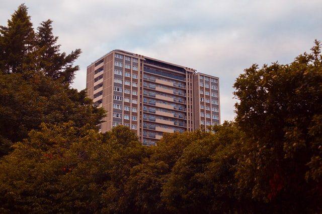 hinter mehreren Bäumen ist ein ziegelfarbiges Hochhaus zu sehen