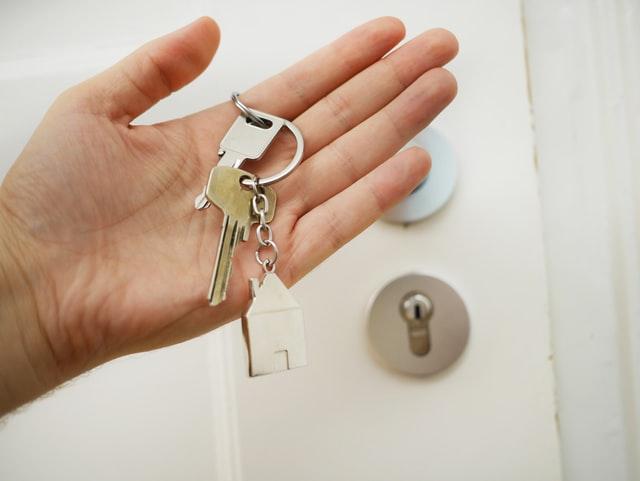 eine Hand vor einer weißen Wohnungstür die einen Hausschlüssel hält