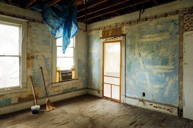 eine etwas ältere Wohnung ohne Tapeten an den Wänden und einer blauen Plastiktüte die von der Decke hängt