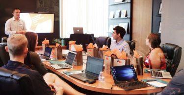 in einem Konferenzraum sitzen sechs sommerlich gekleidete Personen mit ihren Laptops