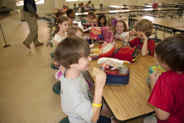 der Tisch einer Schulkantine an dem mehrere Schüler sitzen und fröhlich essen