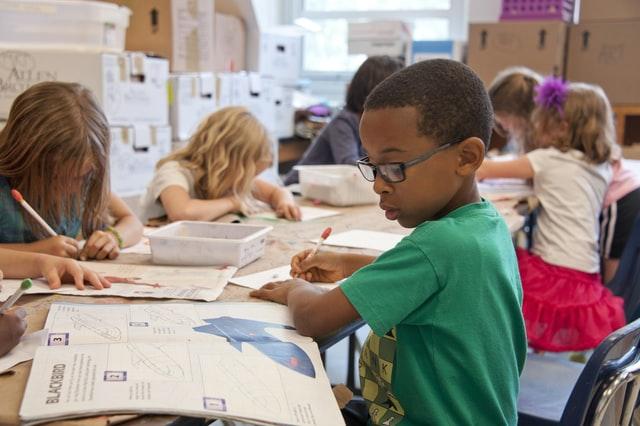 in einer Schulklasse sitzen mehrere Kinder an einem langem Tisch und sehen in ein Buch oder schreiben etwas