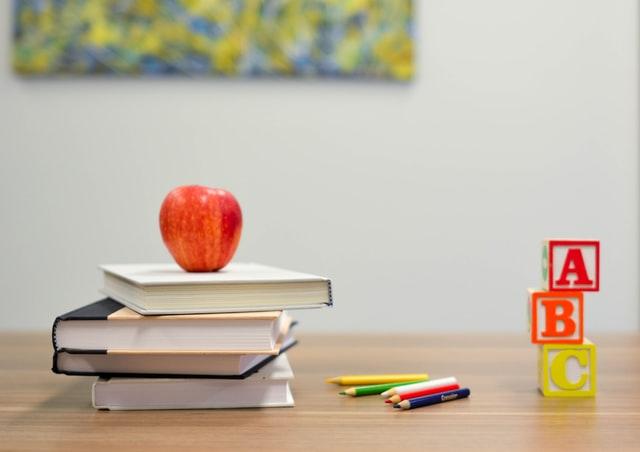 ein Holztisch auf dem vier Bücher aufeinander liegen und darauf ein roter Apfel, daneben mehrere Buntstifte und ganz rechts Würfel mit Buchstaben