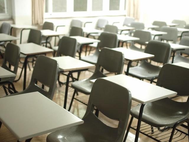 ein leeres Klassenzimmer in dem die leeren Stühle und Tische zu sehen sind