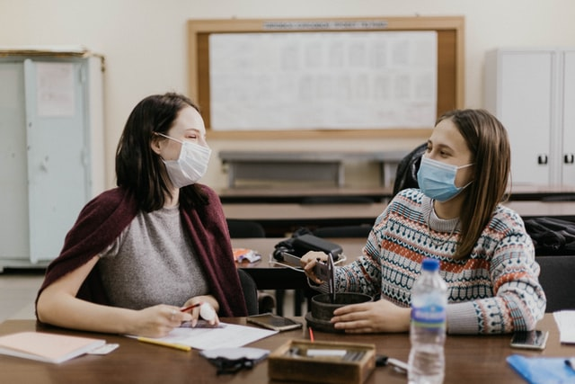 zwei Lehrerinen einer Schule die an einem Tisch eines Klassenzimmers sitzen und fröhlich sind