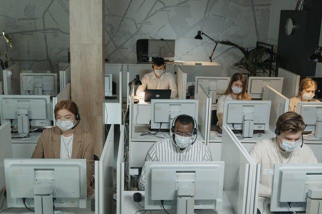 das Büro einer Firma in der mehrere Mitarbeiter an weißen Computern sitzen