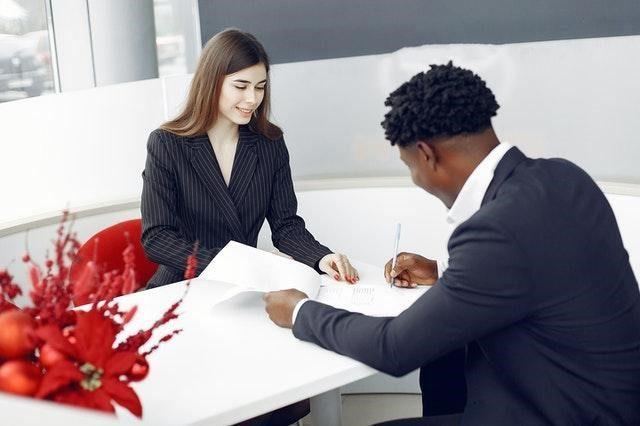 ein Mann und eine Frau, beide in dunklen Anzügen sitzen sich gegenüber an einem weißen Tisch und überprüfen verschiedenen Dokumente