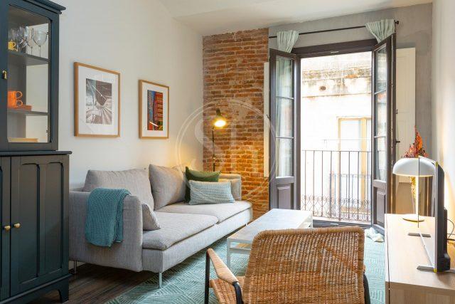 das Wohnzimmer einer Mietwohnung, es hat einen kleinen Balkon, ein graues Sofa, einen rechteckigen kleinen Tisch und darunter einen türquiesen Teppich