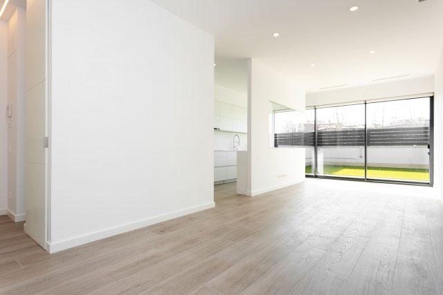 eine leersetehende Wohnung mit weißen Wänden und hellem Parketboden