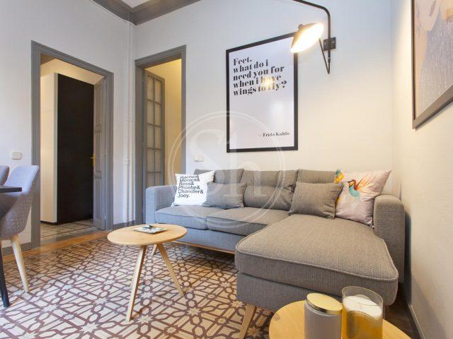 das Wohnzimmer einer Ferienwohnung mit einem großen grauen Sofa und einem kleinen runden Holztisch davor