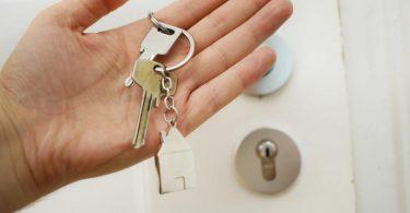 eine Hand mit einem Hausschlüssel vor einer weißen verschloßenen Tür