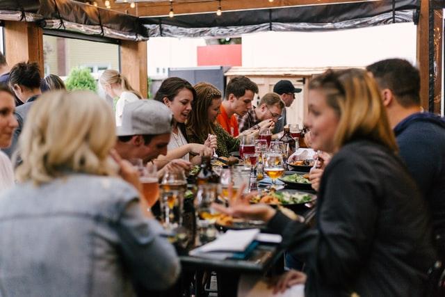 ein Straßenfest wo gerade alle Nachbarn zusammen sitzen, essen und sich angeregt unterhalten