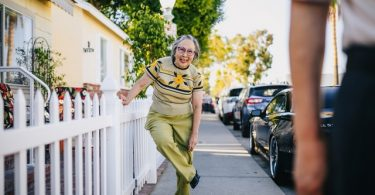 eine ältere Frau die sich an einem weißen Gartenzaun festhält um sich ihre grüne Hose zurechtzurücken