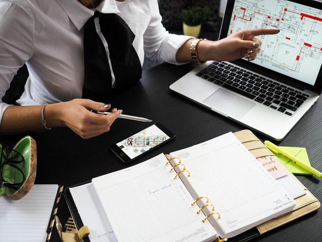 schwarzer Schreibtisch mit offenem Terminkalender und Verwalterin die auf Pläne am Computer und Handy weist