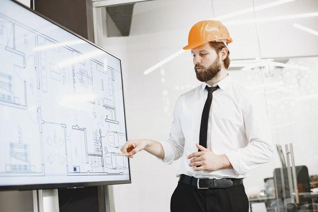ein Hausverwalter mit orangenem Helm der gerade etwas auf einem Hausplan zeigt